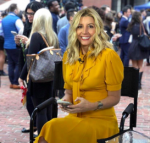 Sarah Blakely, founder of Spanx, sitting and smiling in a yellow dress
