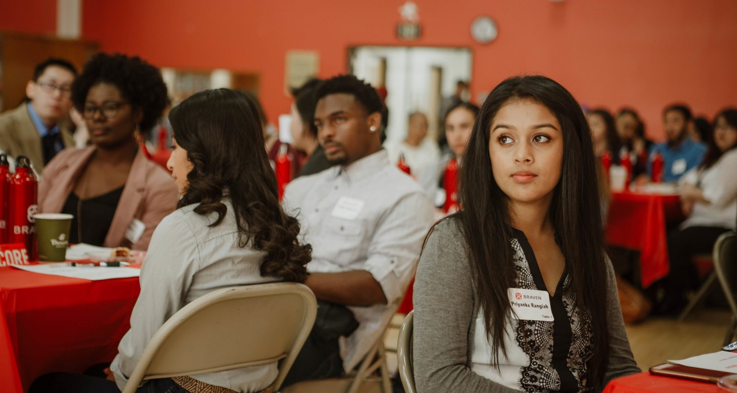 female student looking over her shoulder while sitting at networking event
