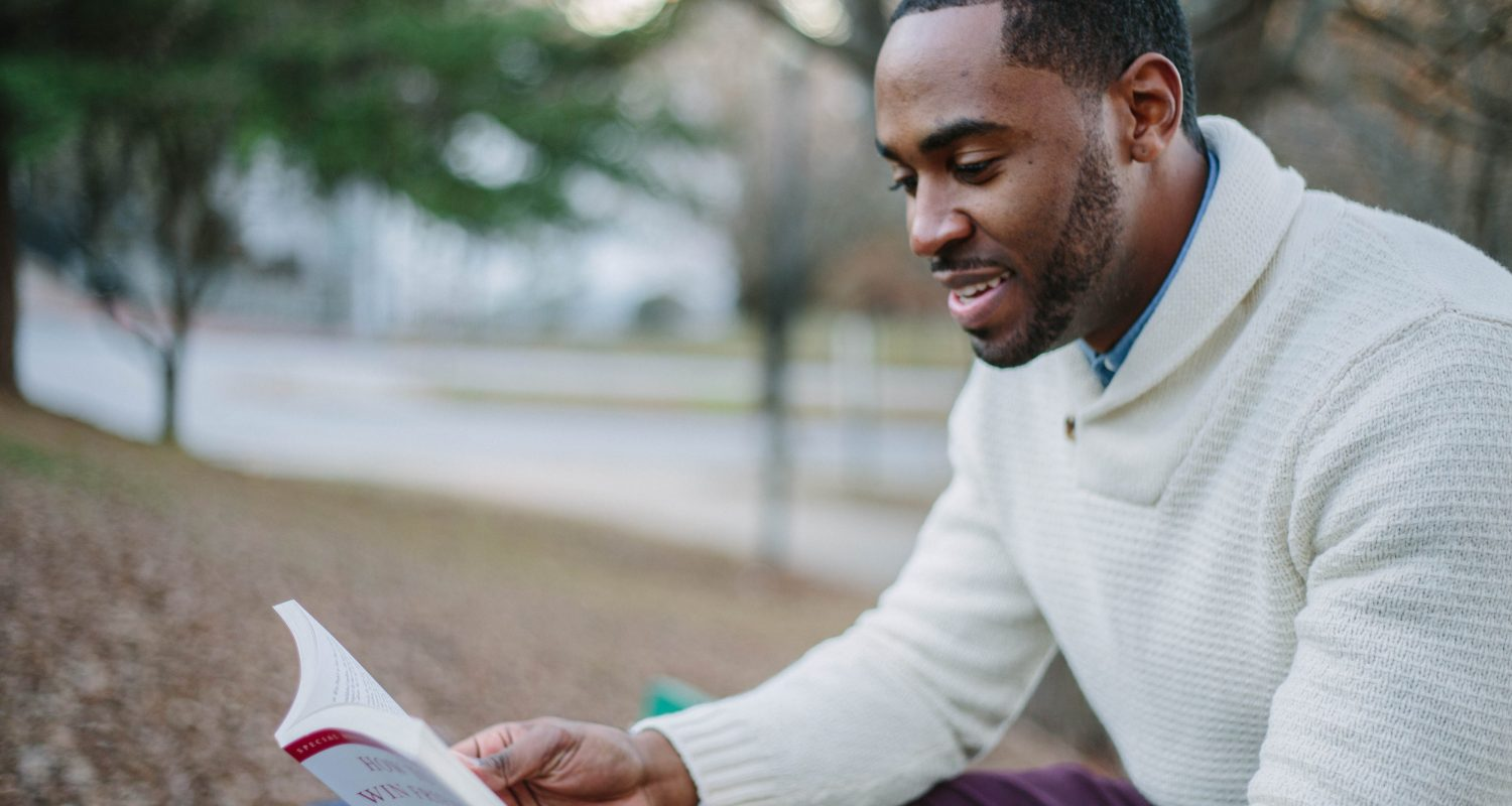 African American teen male reading a book on a bench in the park