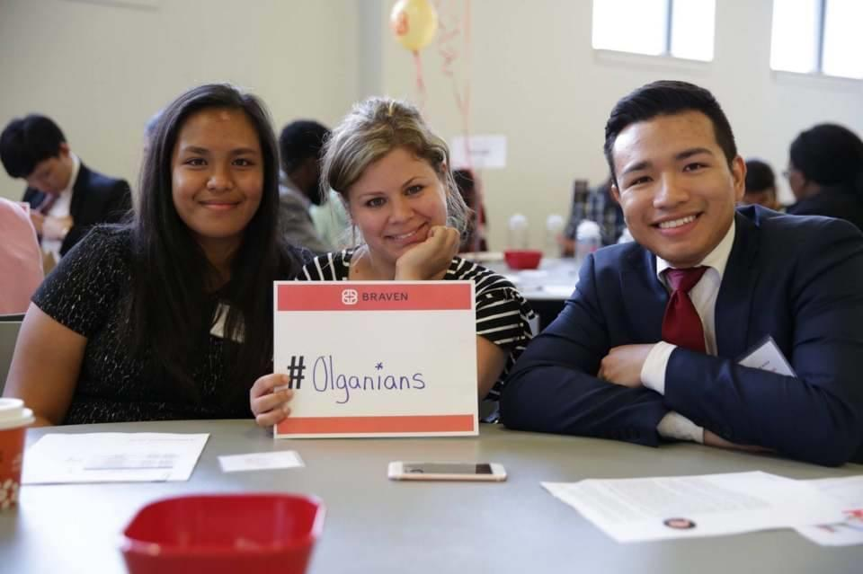 two women and a man sitting at a table and smiling with a sign